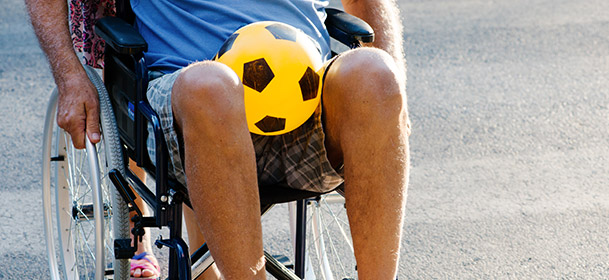 Man in wheel chair with soccer ball