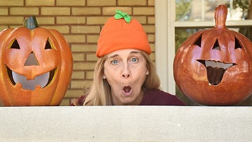 Dentist making funny faces with pumpkins