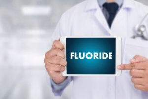 "a doctor holding a sign that reads ""Fluoride"""