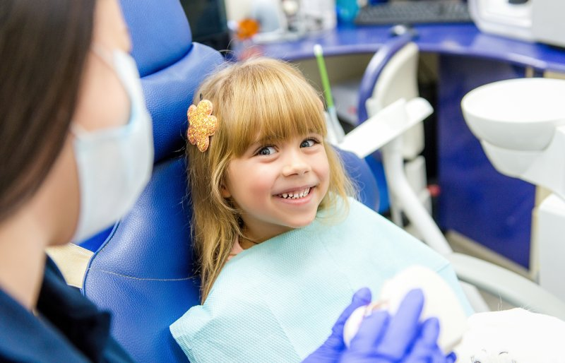 a little girl with a flower clip in her hair smiles at her dentist during a visit